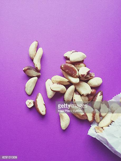 high angle view of brazil nuts on purple background - brazil nut stock photos and pictures