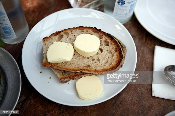 High Angle View Of Bread And Butter Served In Plate On Wooden Table