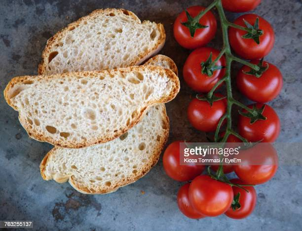 High Angle View Of Bread And Cherry Tomatoes On Slate