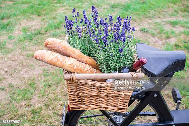 high angle view of bread with lavender flowers and wine bottle in bicycle basket - fahrradkorb stock-fotos und bilder