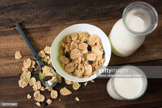 High Angle View Of Breakfast Cereal By Milk Glass In Bowl On Wooden Table