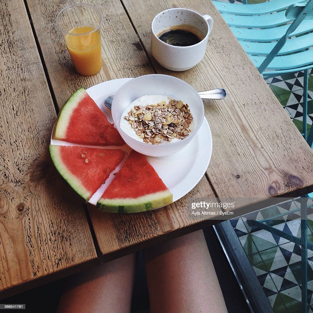 High Angle View Of Breakfast Cereal With Watermelon In Plate By Coffee Cup : Stock Photo