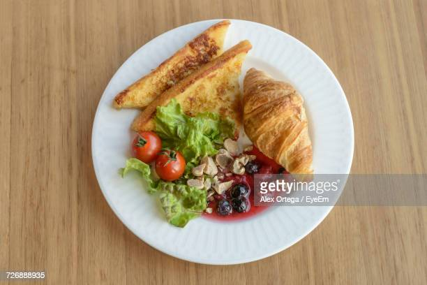 High Angle View Of Breakfast In Plate On Wooden Table