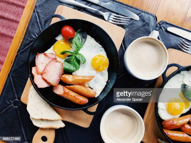 High angle view of breakfast with fried eggs, sausage and bacon served in a skillet