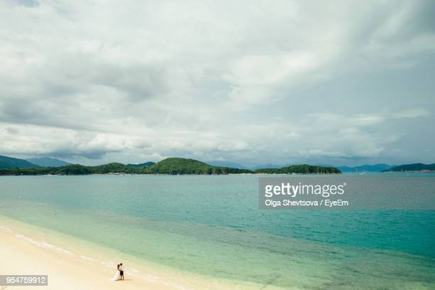 High Angle View Of Bride And Groom Standing At Beach
