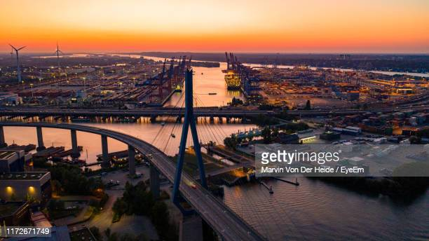 high angle view of bridge over river amidst buildings in city - köhlbrandbrücke stock photos and pictures