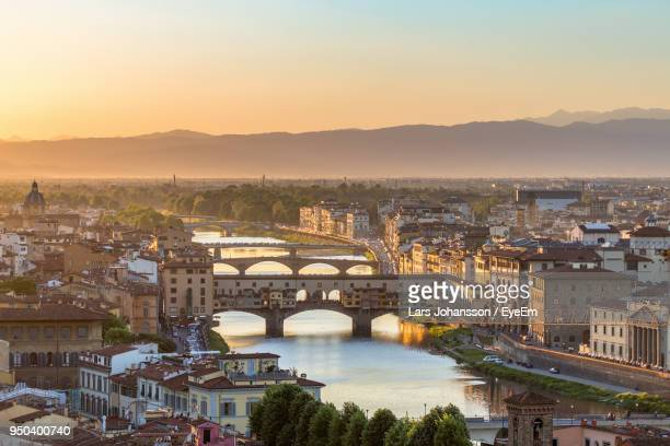 high angle view of bridge over river at sunset - ponte vecchio stock photos and pictures