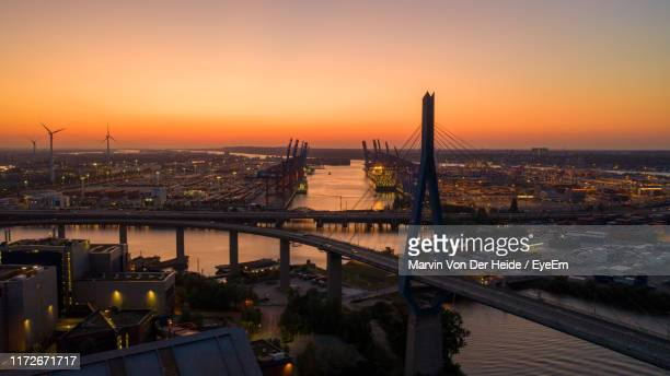 high angle view of bridge over river by buildings against sky during sunset - köhlbrandbrücke stock photos and pictures