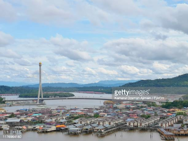 high angle view of bridge over river by buildings in city - brunei stock pictures, royalty-free photos & images