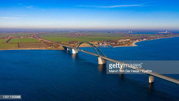 high angle view of bridge over sea against sky - fehmarn stock-fotos und bilder