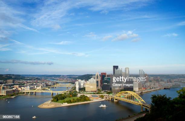 High angle view of bridges over river in Pittsburgh city against blue sky