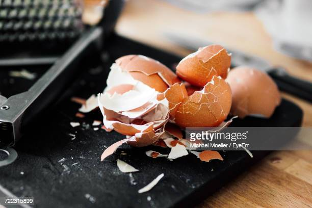 High Angle View Of Broken Brown Eggshells On Cutting Board
