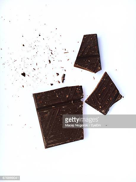 high angle view of broken chocolate on white background - chocolate stock pictures, royalty-free photos & images