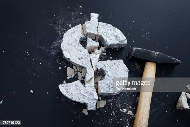High angle view of broken concrete Dollar sign with hammer on table