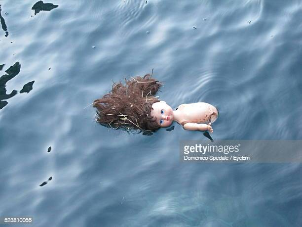 High Angle View Of Broken Doll Floating On Water