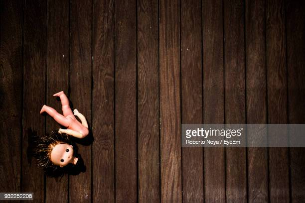 High Angle View Of Broken Doll On Wooden Table