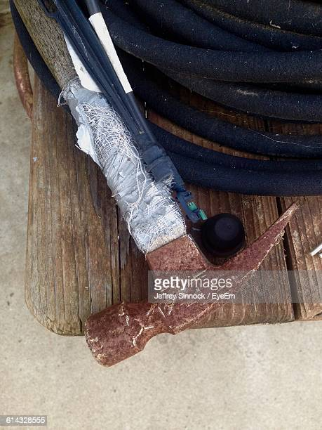 High Angle View Of Broken Hammer With Garden Hose On Table