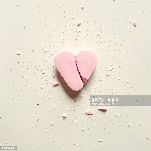 High Angle View Of Broken Heart Shape Candy On White Table