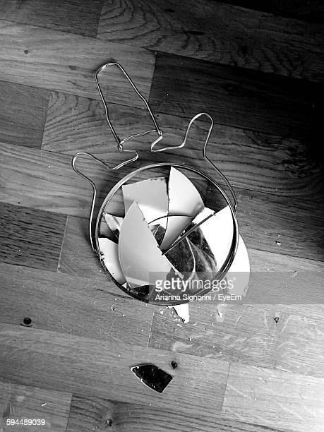 High Angle View Of Broken Mirror On Hardwood Floor