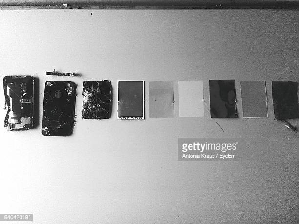 High Angle View Of Broken Mobile Phone Arranged On Table