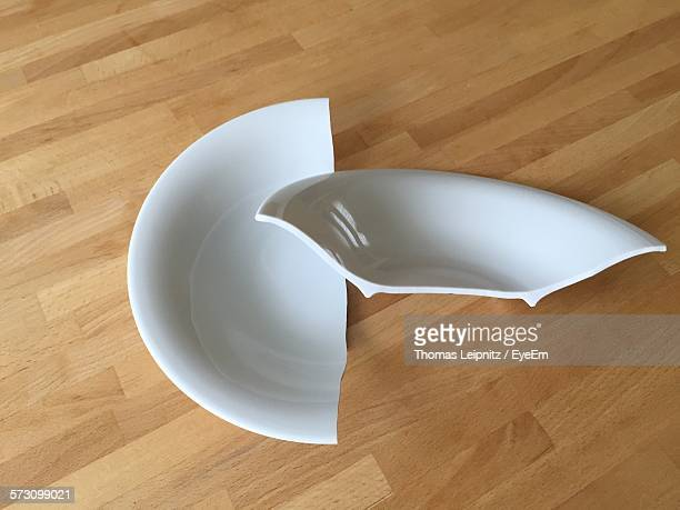 High Angle View Of Broken Plate On Wooden Table