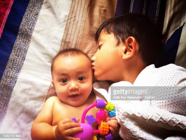 High Angle View Of Brother Kissing Cute Sister While Lying On Bed At Home