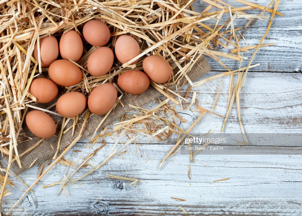 High Angle View Of Brown Eggs With Straws On Table : Stock Photo