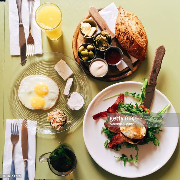 High angle view of brunch table for two with Israeli snacks, hummus, bread, fried eggs, salad, beef meat, olives and cheese