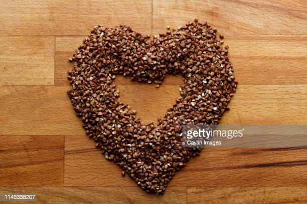 high angle view of buckwheat arranged in heart shape on wooden table - buckwheat stock pictures, royalty-free photos & images