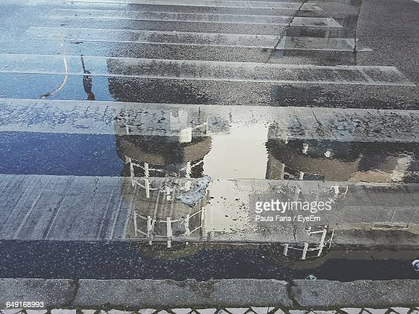 High Angle View Of Building Reflection In Puddle On Street