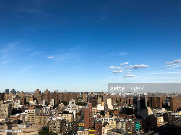 high angle view of buildings against blue sky - lower east side manhattan stock pictures, royalty-free photos & images