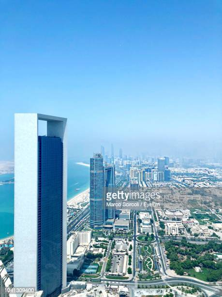 high angle view of buildings against clear blue sky - abu dhabi stock pictures, royalty-free photos & images