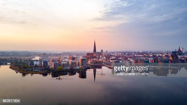 high angle view of buildings against cloudy sky during sunset - rostock stock pictures, royalty-free photos & images