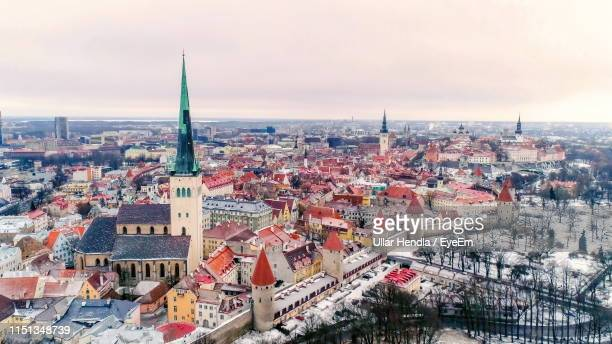 high angle view of buildings against cloudy sky in town - tallinn stock-fotos und bilder