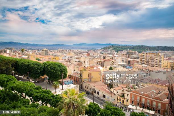 high angle view of buildings against cloudy sky - cagliari stock pictures, royalty-free photos & images
