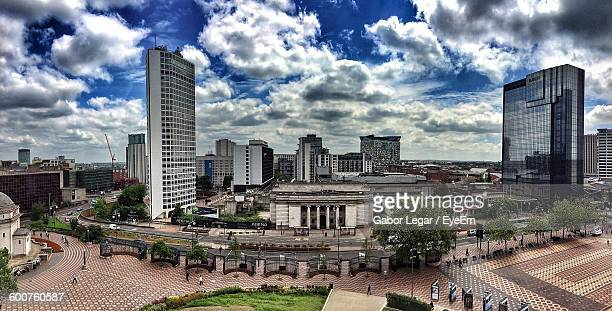 high angle view of buildings against cloudy sky - birmingham england stock photos and pictures