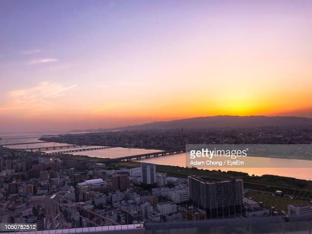 high angle view of buildings against sky during sunset - 町 ストックフォトと画像