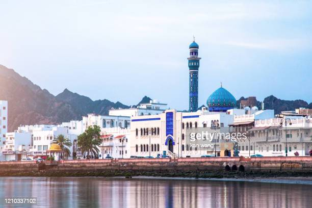 high angle view of buildings and mountains against sky - stock photo photo taken in muscat, oman - wang he stock pictures, royalty-free photos & images