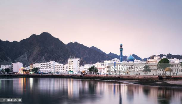 high angle view of buildings and mountains against sky - stock photo photo taken in muscat, oman - oman stock pictures, royalty-free photos & images