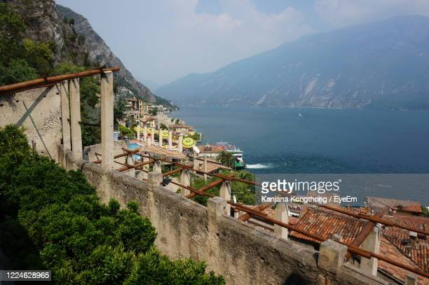 high angle view of buildings and sea against mountains - kanjana kongthong foto e immagini stock