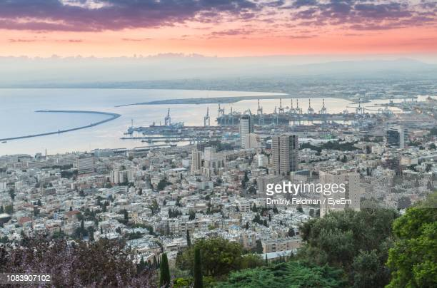 high angle view of buildings and sea against sky during sunset - haifa stock pictures, royalty-free photos & images