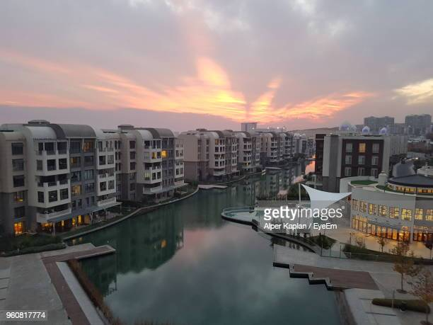 High Angle View Of Buildings By Canal Against Sky During Sunset