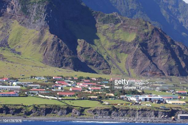 high angle view of buildings by mountain - tristan da cunha eiland stockfoto's en -beelden