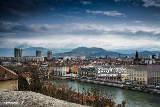 high angle view of buildings by river against cloudy sky - grenoble stock pictures, royalty-free photos & images