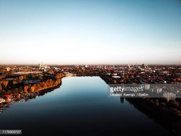 high angle view of buildings by river in town against sky - hanover germany stock pictures, royalty-free photos & images