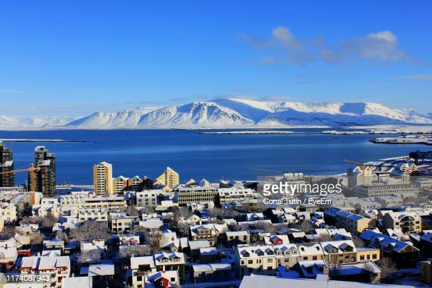high angle view of buildings by sea against blue sky - reykjavik stock pictures, royalty-free photos & images