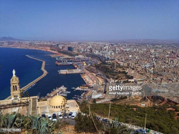 high angle view of buildings by sea against clear sky in oran, algeria - oran algeria photos et images de collection