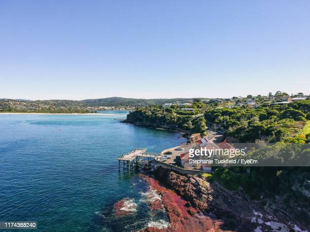 high angle view of buildings by sea against clear sky - merimbula stock pictures, royalty-free photos & images