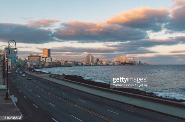 high angle view of buildings by sea against sky during sunset - bortes stock pictures, royalty-free photos & images