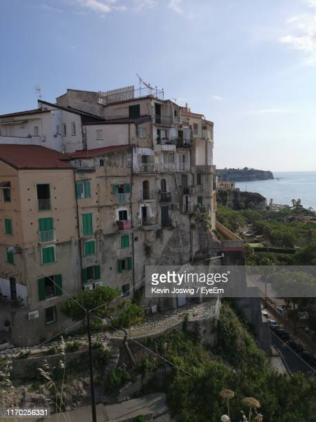high angle view of buildings by sea against sky - low angle view photos et images de collection